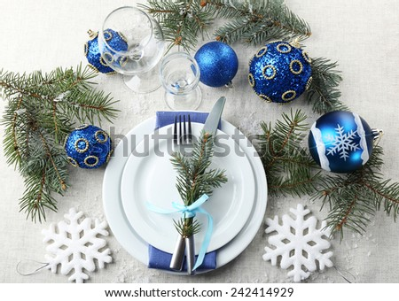 Stylish blue and white Christmas table setting on grey tablecloth background - stock photo