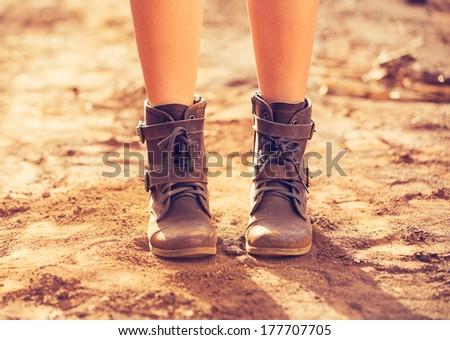 Stylish Boots, Close up view of woman wearing stylish boots on dusty road - stock photo