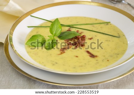 Stylish bowl of ham and potato soup seasoned with pungent serrano peppers and garnished with fresh basil and chives for a hot appetizer to a winter meal - stock photo