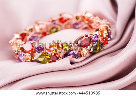 Stylish bracelet with colorful stones on fabric background.
