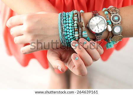 Stylish bracelets and clock on female hand top view - stock photo