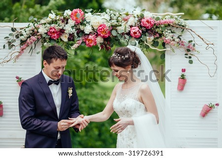 stylish bride and groom are exchange rings on the background flower wedding arch. Happy newlywed - stock photo