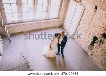 Stylish bride and groom  holding hands in a room with white brick. Loft - stock photo
