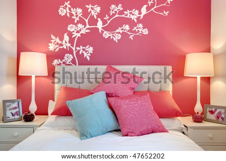 Stylish brightly decorated modern bedroom with wall mural and cushions. Stylish Brightly Decorated Modern Bedroom Wall Stock Photo