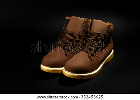 stylish brown nubuck mens boots on black background, advertising concept - stock photo