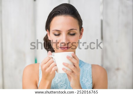 Stylish brunette holding a mug against bleached wooden fence - stock photo