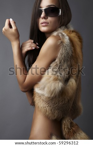 stylish brunette in fox cape and sun glasses. - stock photo
