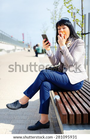 Stylish brunette serious corporate business woman 30-35 years, reading news on smart, mobile phone holding eating apple. sunny day, good weather, city street, Human face expression. Social media app - stock photo