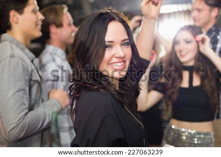 Stylish brunette smiling at camera at the bar
