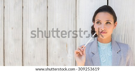 Stylish brunette thinking and smiling against bleached wooden fence - stock photo