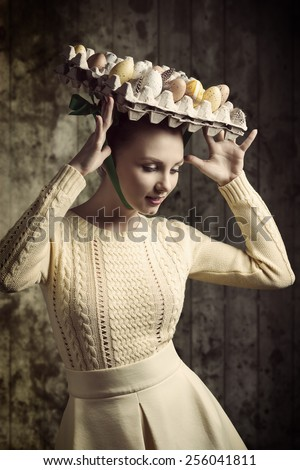 stylish brunette woman with yellow dress posing in easter shoot with easter eggs in the carton box on her head like a bizarre hat  - stock photo