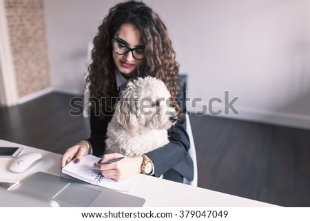 Stylish brunette working from home in her home office and holding her dog in her lap. Depth of field, selective focus - stock photo