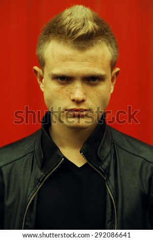 Stylish bully concept. Portrait of brutal young man with short hair wearing black jacket and posing over red urban background. Wet colored hair. Hipster style. Close up. Outdoor shot - stock photo