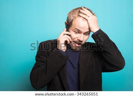 stylish business man anxiously on the phone, with a beard and mustache, office style studio shot on isolated blue background - stock photo