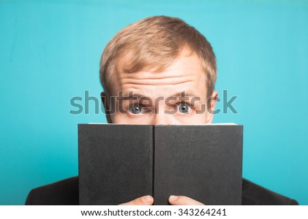 stylish business man hiding behind the book, with a beard and mustache, office style studio shot on isolated blue background