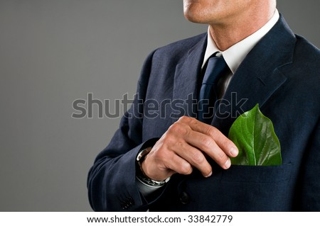 Stylish businessman holding a fresh green leaf in his pocket. Green business concept, take care of the environment! - stock photo