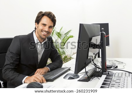 Stylish businessman in a suit sitting at his desk in the office chatting on the phone with a view of his blank computer monitor - stock photo