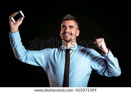 Stylish businessman on black background. Businessman cheerfully rejoicing and holding mobile phone - stock photo