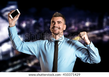 Stylish businessman on night cityscape background. Businessman cheerfully rejoicing and holding mobile phone - stock photo