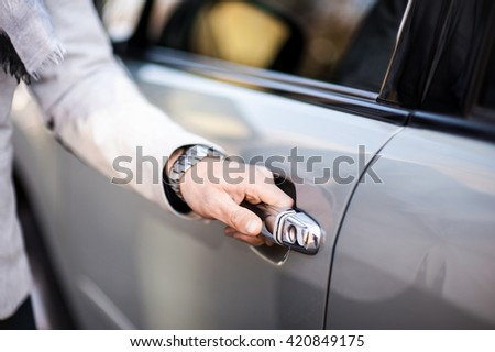 Stylish businessman opens the door of his car