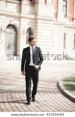 Stylish businessman walking outdoors and looking away