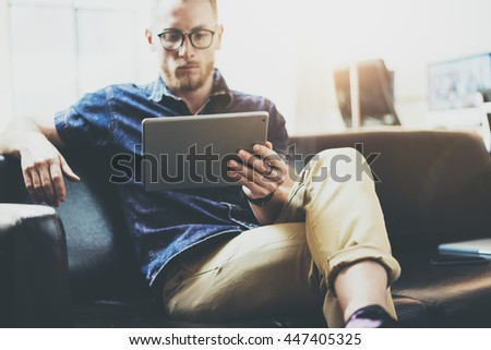 Stylish Businessman working tablet PC modern Interior Design Loft Office.Man relax Vintage sofa use contemporary device Hand.Blurred Background.Creative Business Startup Idea.Horizontal,Film effect - stock photo