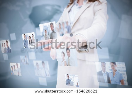 Stylish businesswoman presenting coworkers pictures on digital interface - stock photo