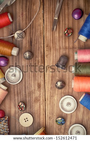 stylish buttons,needles,thread laid out on the wooden table - stock photo