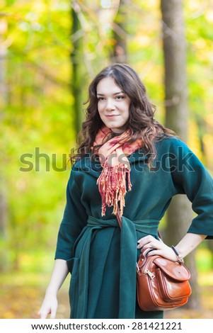 Stylish Caucasian Female Brunette Model Posing in Autumn Forest and Smiling. Vertical Image Composition - stock photo