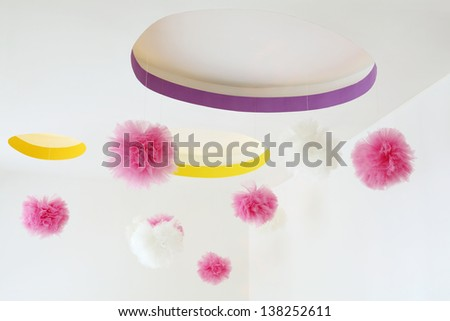 Stylish ceiling with dangling pink and white pom-poms in kids room. - stock photo