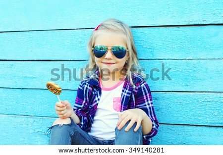 Stylish child with sweet caramel lollipop over colorful blue background - stock photo