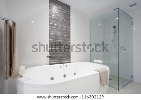 Stylish clean bathroom with shower and bath tub - stock photo