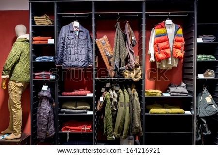 Stylish clothes on hangers in shop  - stock photo