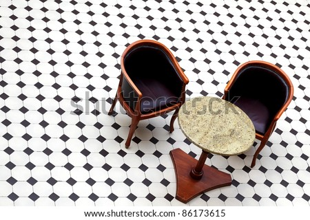 Stylish coffee table and pair empty leather armchairs in black and white checkerboard - stock photo