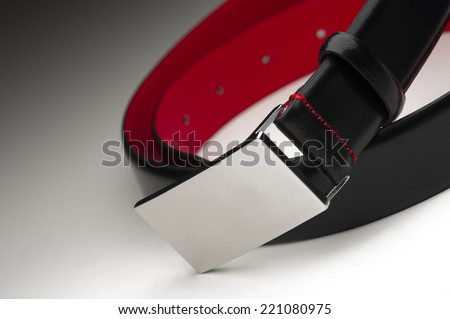 Stylish coiled mens black leather belt with a brushed metal silver buckle and colorful crimson lining, close up view on a graduated grey background - stock photo