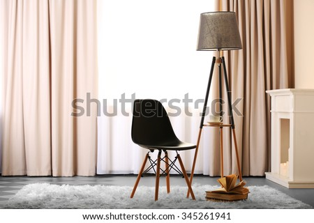 Stylish conception with chair and lamp on light room background - stock photo