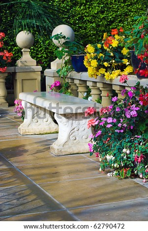 Stylish concrete bench surrounded by flowers on a patio