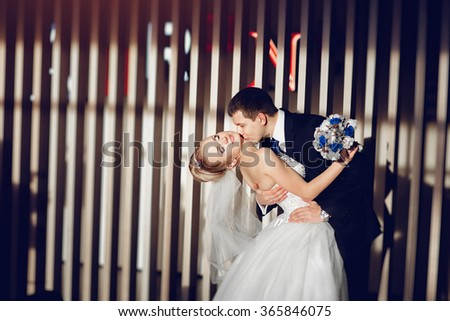 Stylish couple in love the bride and groom are dancing, kissing and cuddling in the modern and stylish interior of the restaurant. - stock photo