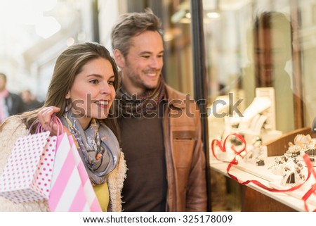 Stylish couple is looking at wedding rings. A grey hair man with beard and a woman with two shopping bags are standing in front of a jewelry shop. They are looking at the shop window. - stock photo
