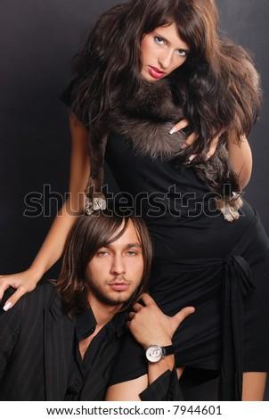 Stylish couple posing - black background - stock photo