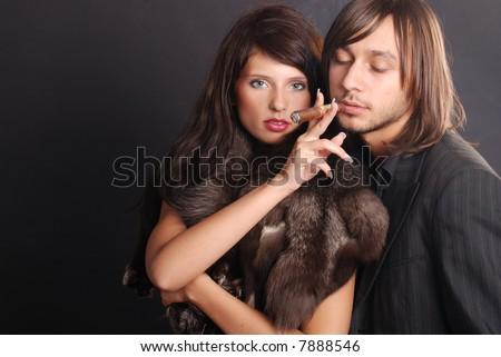 Stylish couple smoking a cigar on black background - stock photo