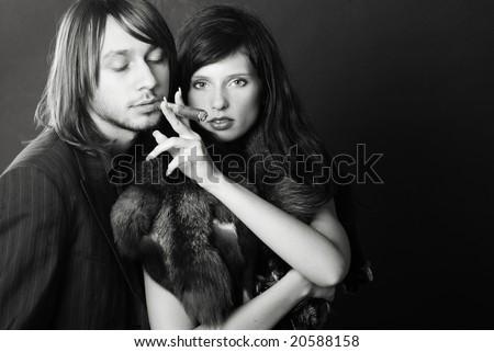 Stylish couple smoking a cigar on black background - black and white - stock photo