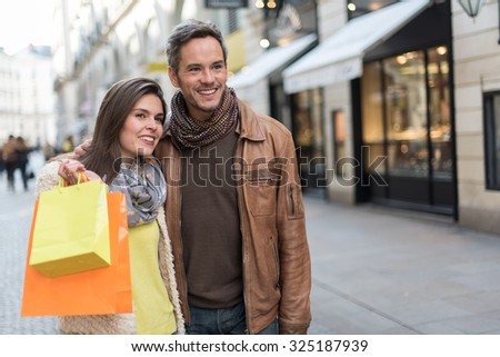 Stylish couple standing in a cobbled car-free street. The grey hair man with beard is wearing a brown leather coat and the woman a yellow top and two shopping bags, they also have scarfs - stock photo