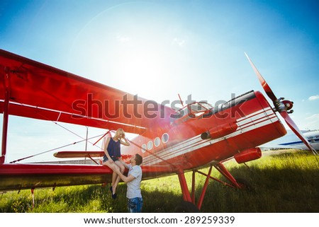 Stylish couple standing near a plane at the airport. honeymoon  - stock photo