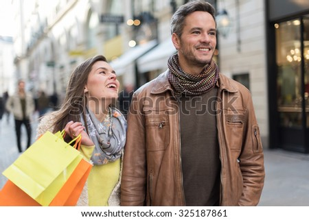 Stylish couple walking in a cobbled car-free street. The grey hair man with beard is wearing a brown leather coat and the woman a yellow top and two shopping bags, they also have scarfs - stock photo