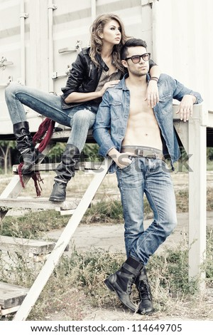 stylish couple wearing jeans and boots posing dramatic - retro processed image - stock photo