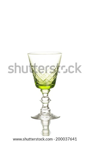 Stylish cut glass green tinted wineglass or goblet on a decorative stem with a diamond pattern in the glass  with copy space, vertical format - stock photo