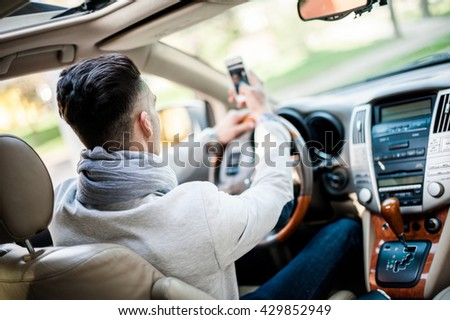 Stylish driver inside his own luxury car make photo by phone - stock photo