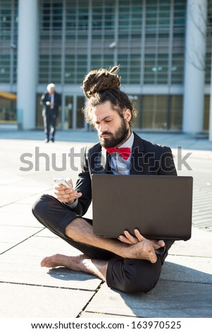 Stylish elegant dreadlocks businessman using notebook in business landscape
