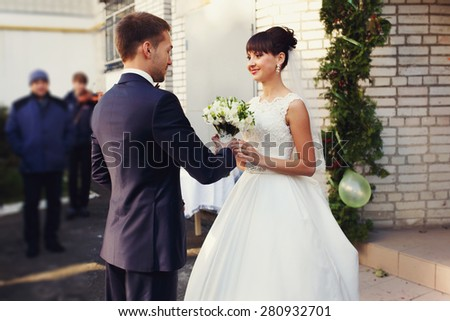 Stylish elegant groom gives the bride smiling lovely bouquet of peonies